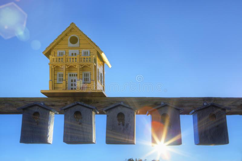 Contrasting bird boxes. An extravagant bird box above a collection of mundane bird boxes at sunset royalty free stock images