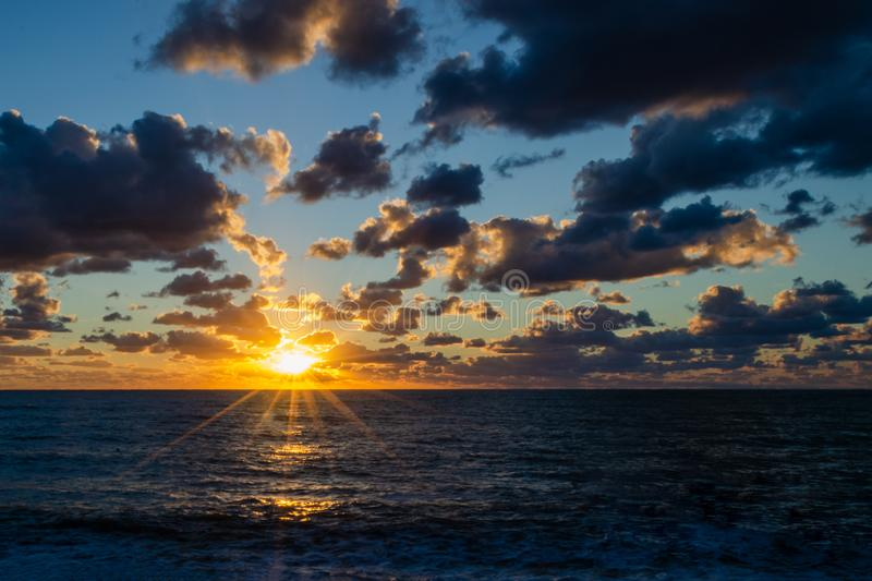 Contrasting evening seascape with ripples. A sun disk with rays illuminates the warm light of the dramatic clouds and sea surface. Contrasting evening seascape stock photo