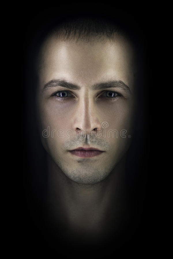 Contrasting male portrait on black background. Light and shadow on the man`s face. Stylish, brutal man, art photo. Silhouette face royalty free stock photos