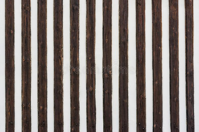 Contrasting striped texture. Decorative wood battens. White painted wall with vertical stripes of old brown knotted planks. Original wooden background. Idea a stock image