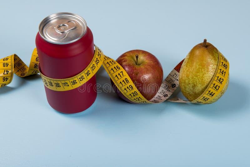 contrasto sano di vita con la latta di soda e la frutta con una misura di nastro fotografia stock