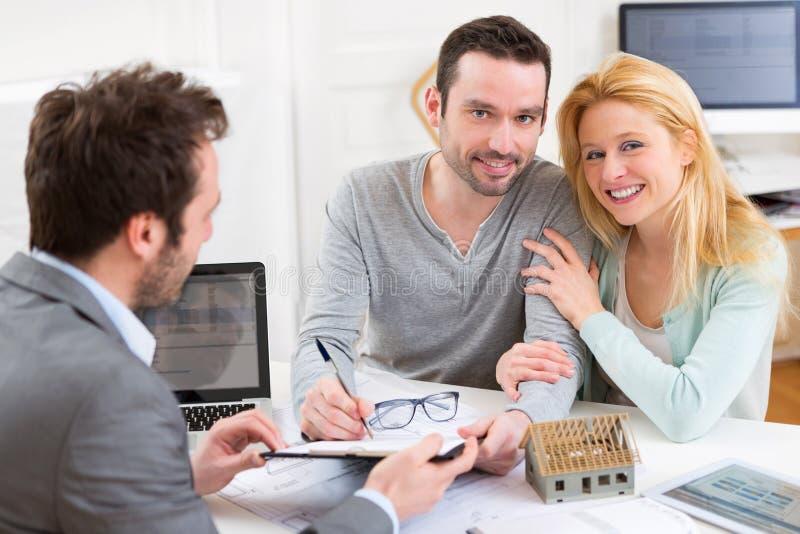Contrat de signature de jeunes couples attrayants avec le vrai agent immobilier photo stock