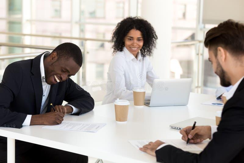 Contrat de signature de travailleur enthousiaste d'Afro-américain lors de la réunion d'affaires photos stock