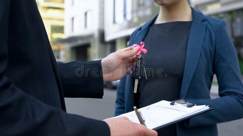 Contrat de signature de vendeur en vente de voiture, présentant des clés à l'acheteuse, fin  photos stock