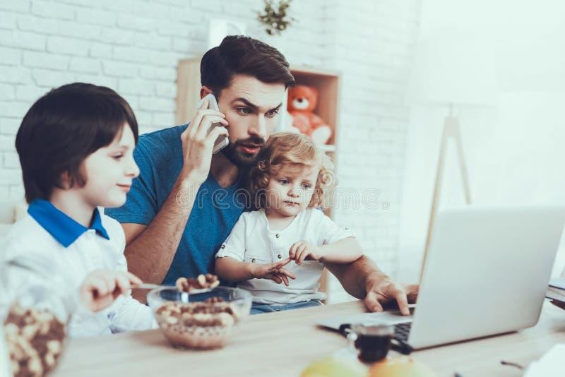 Contratan al padre a criar a niños mientras que Workes imágenes de archivo libres de regalías