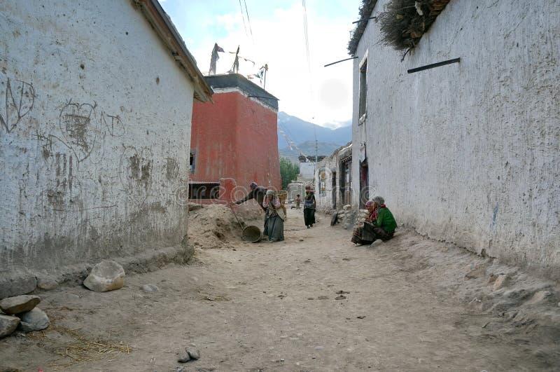 Contratan a los residentes locales en las calles del pueblo de Tsarang por la tarde a sus propios asuntos imagen de archivo libre de regalías
