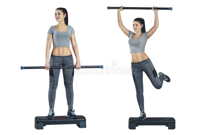 Contratan a una muchacha a aeróbicos del paso con la barra de cuerpo en sus manos en un blanco, fondo aislado imagen de archivo libre de regalías