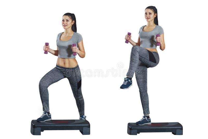 Contratan a una muchacha a aeróbicos del paso con pesas de gimnasia en sus manos en un blanco, fondo aislado fotografía de archivo libre de regalías