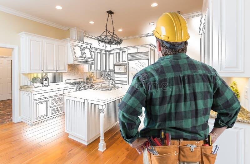 Contratante masculino na correia do capacete de segurança e da ferramenta que olha o desenho da cozinha fotos de stock
