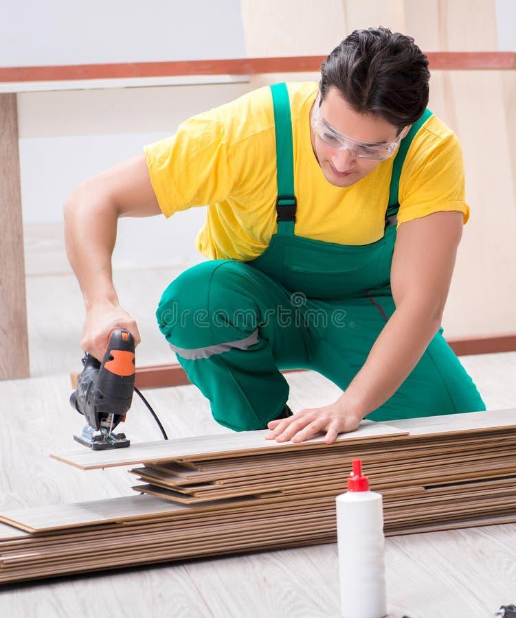 Contratante que trabalha no assoalho de madeira estratificado imagens de stock royalty free