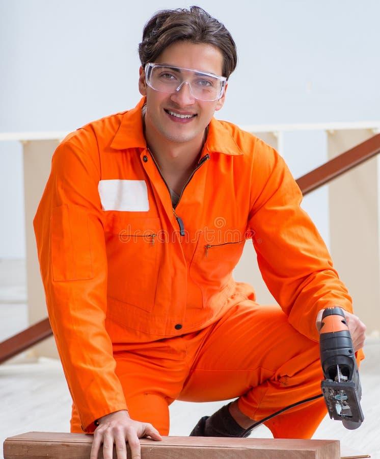 Contratante que trabalha no assoalho de madeira estratificado foto de stock