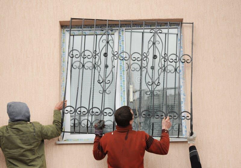 Contratantes do construtor que instalam barras da segurança do ferro da janela para a proteção fotografia de stock