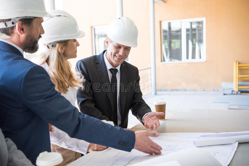 Contratantes no vestuário formal que trabalha com os modelos na construção fotos de stock royalty free
