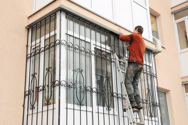 Contratista de obras que instala barras de la seguridad del hierro de la ventana del balcón Rejilla del metal para las ventanas y fotografía de archivo