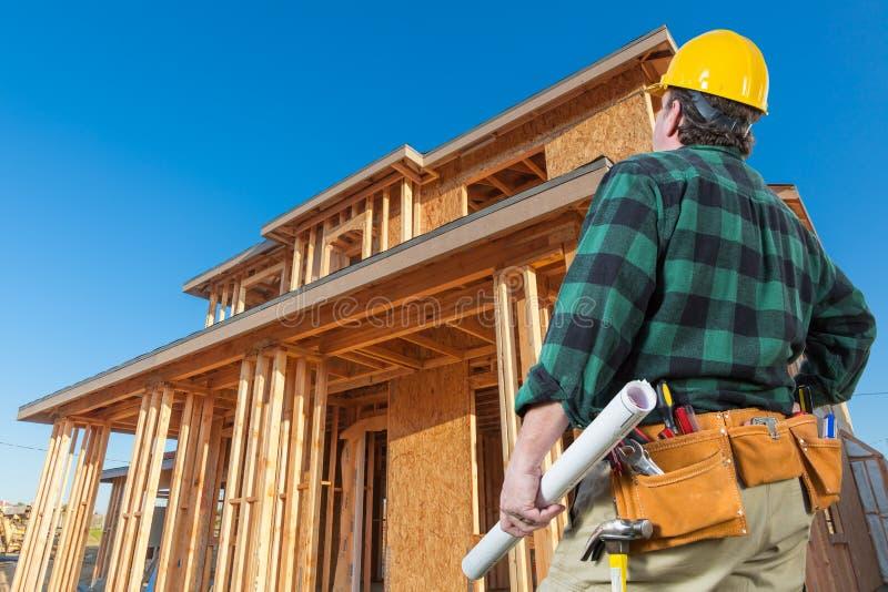 Contratista en Front New House Wood Framing en el emplazamiento de la obra foto de archivo libre de regalías