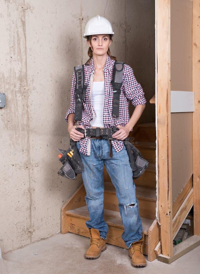 Contratista femenino joven con el equipo del carpintero foto de archivo