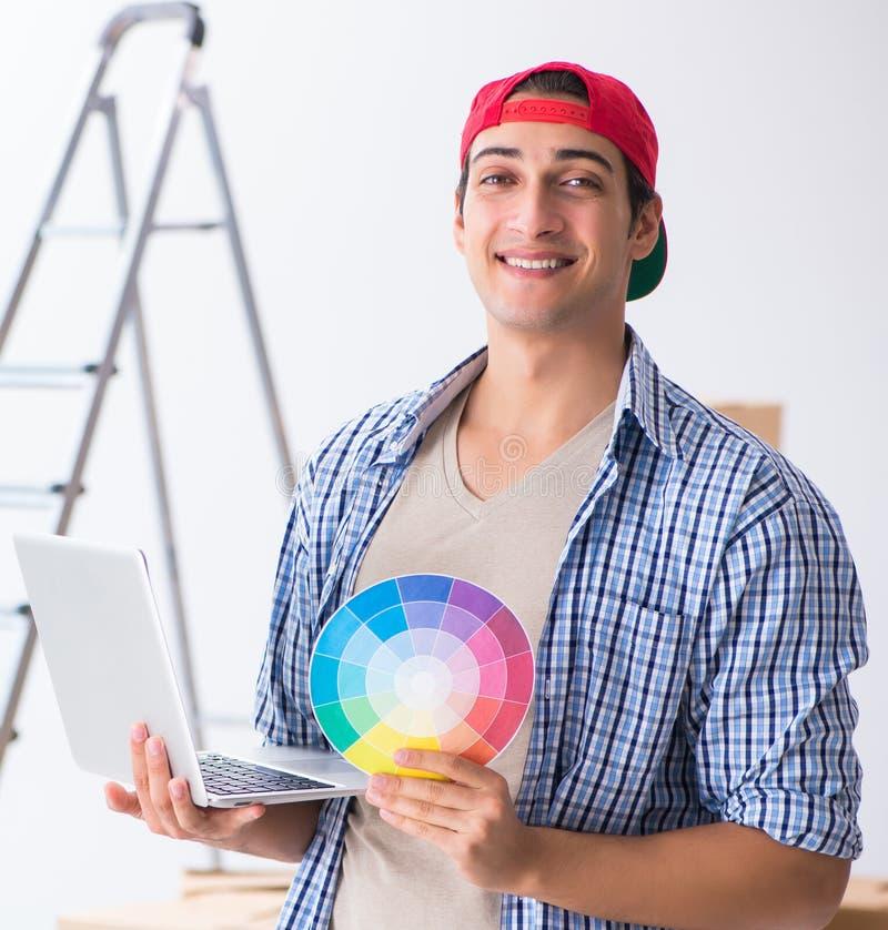 Contratista joven del pintor que elige los colores para la renovaci?n casera foto de archivo libre de regalías