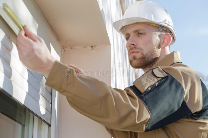 Contratista joven que instala persianas de ventana fotografía de archivo