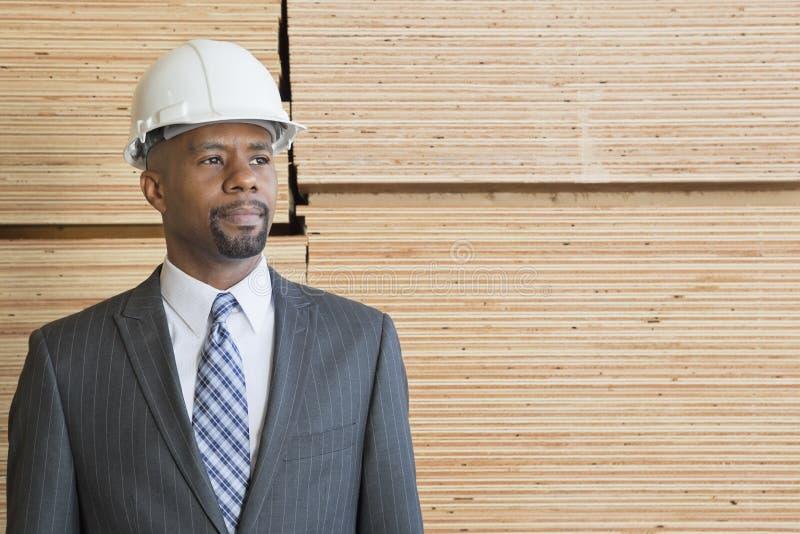Contratista masculino afroamericano confiado que parece ausente mientras que se coloca delante de tablones de madera apilados imagen de archivo