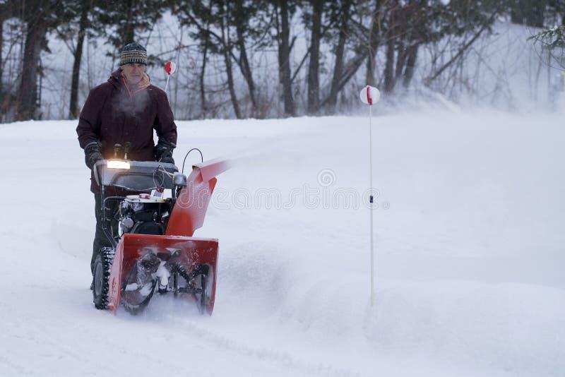 Contratista que despeja la calzada residencial de nieve en invierno foto de archivo