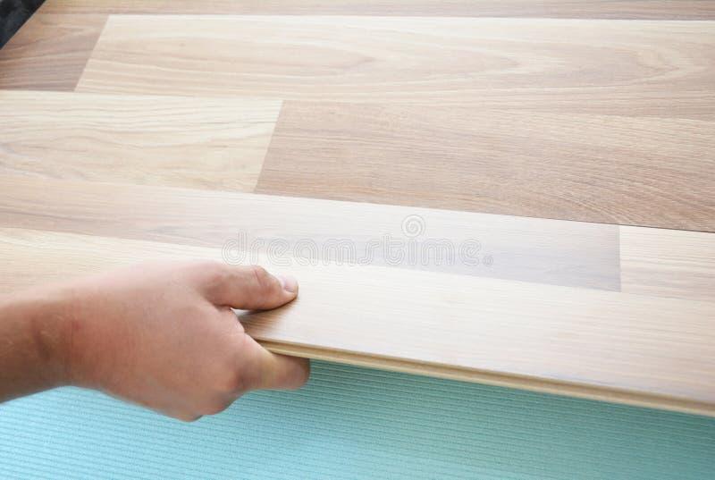 Contratista que instala el suelo laminado de madera con las hojas del aislamiento y de la insonorización Hombre que pone el suelo fotografía de archivo