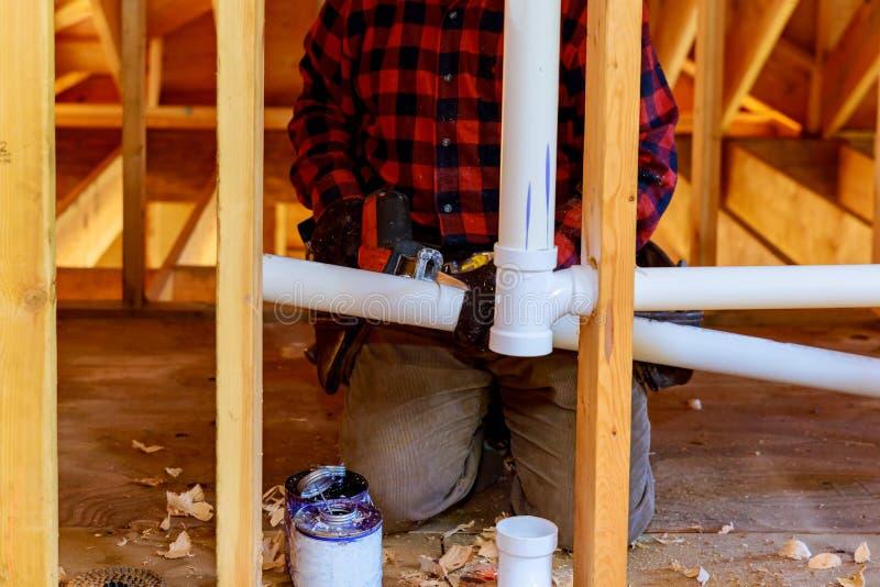 contratista que instala un alcantarillado para una pared en una nueva construcción comercial foto de archivo libre de regalías