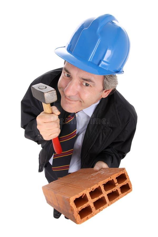 Contratista que sostiene un martillo y un ladrillo imagen de archivo