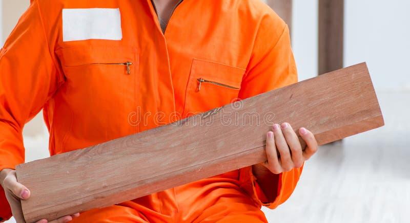 Contratista que trabaja en piso de madera laminado fotos de archivo