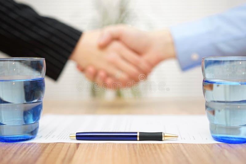 Contrato assinado com aperto de mão no borrão, foco na pena foto de stock