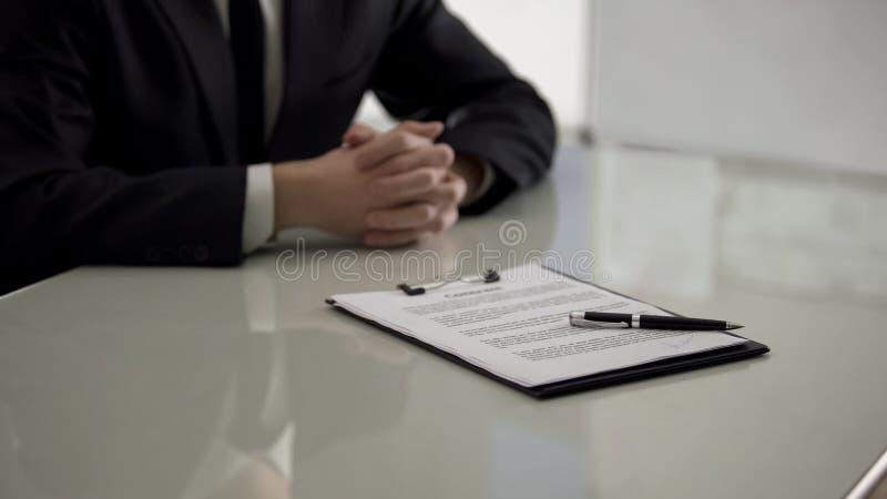 Contrato con la pluma que miente en la tabla, candidato de trabajo masculino en el fondo, empleo imagen de archivo libre de regalías