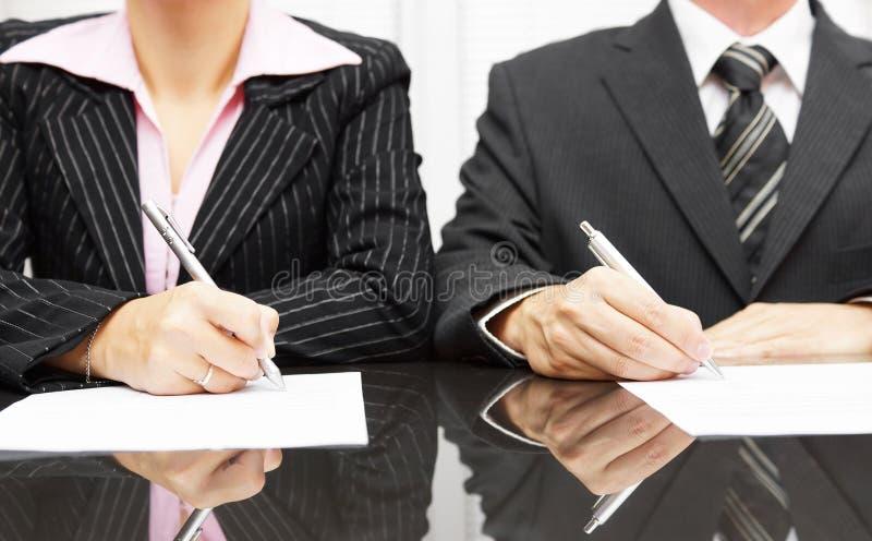 Contrato de assinatura da mulher de negócios e do homem de negócios após a negociação fotografia de stock royalty free