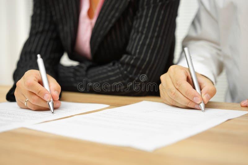 Contrato de assinatura da mulher de negócios e do homem de negócios no escritório imagens de stock