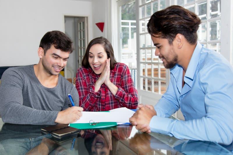 Contrato de assinatura dos pares entusiasmado para própria casa imagens de stock royalty free