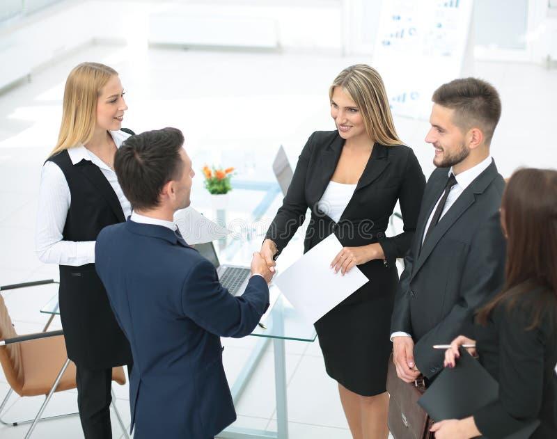 Contrato de conclusão da equipe do negócio da diversidade com aperto de mão na foto de stock