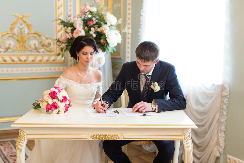 Contrato de firma de la boda de los pares jovenes foto de archivo libre de regalías