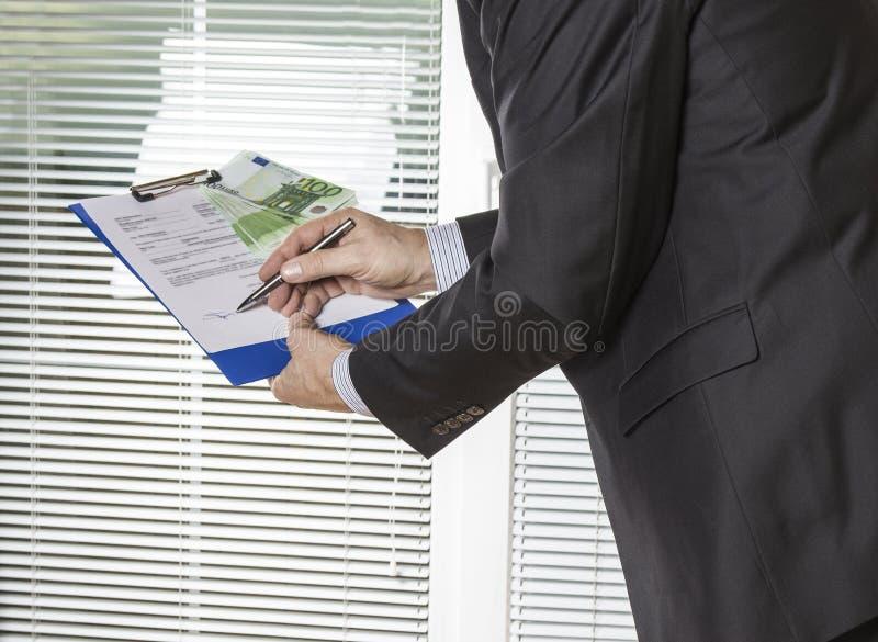 Contrato de firma del hombre de negocios con el dinero del euro del soborno imagenes de archivo