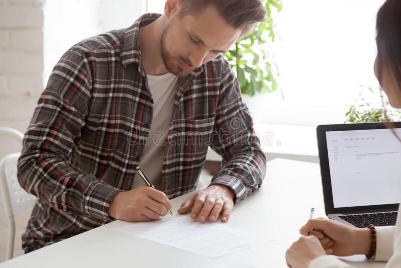 Contrato de trabalho de assinatura focalizado do empregado do sexo masculino após o int bem sucedido imagens de stock