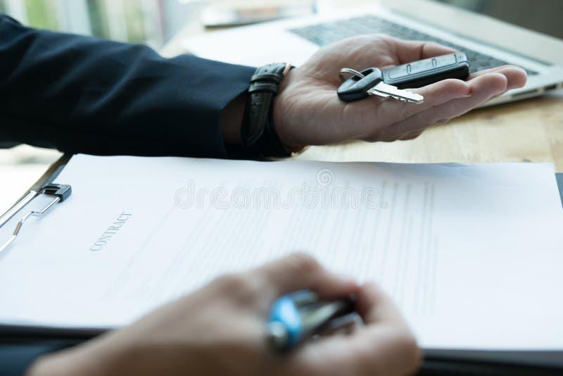 Contrato de vendas de assinatura atual do homem de negócios com chave do carro ao custo fotografia de stock royalty free