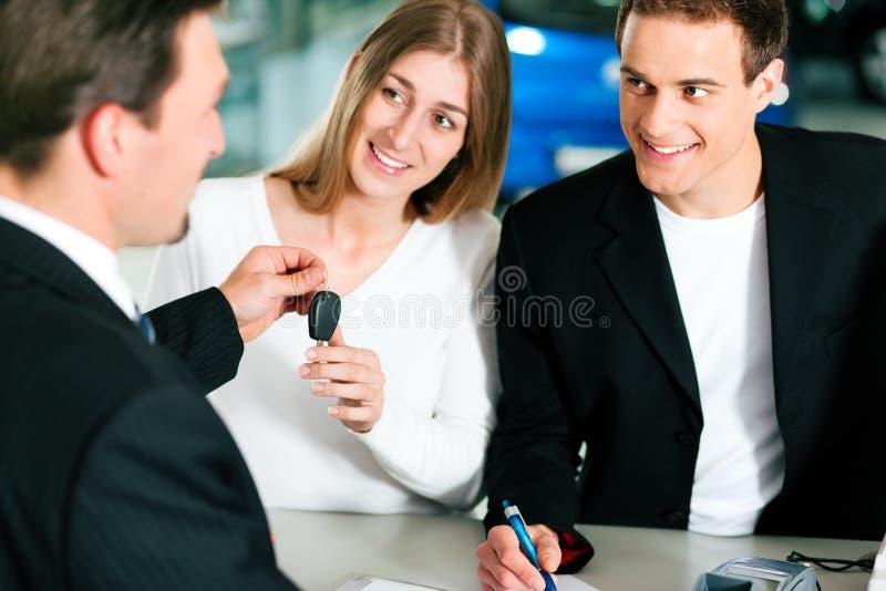 Contrato de vendas de assinatura dos pares no negociante de carro fotografia de stock