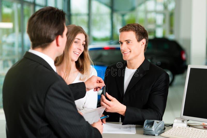 Contrato de vendas de assinatura dos pares no negociante de carro imagem de stock royalty free