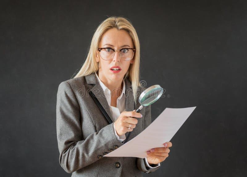 Contrato del negocio de la lectura de la mujer con la lupa foto de archivo