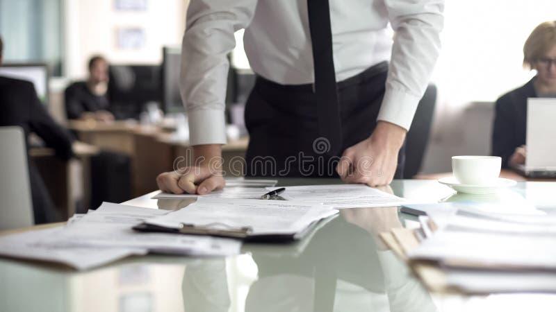 Contrato descontentado da leitura do CEO, inclinando-se na tabela com raiva, relat?rio do erro imagens de stock