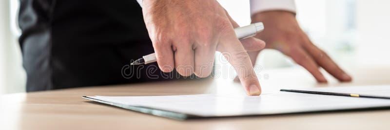 Contrato ou documento da leitura do homem de negócios no dobrador que aponta com foto de stock royalty free