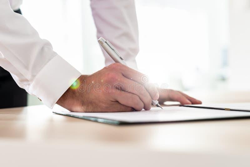 Contrato ou formulário de candidatura de assinatura do homem de negócios fotografia de stock royalty free