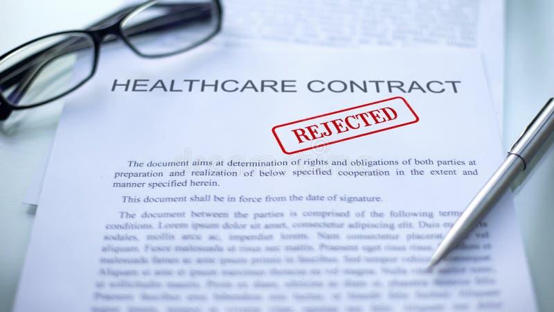 Contrato rejeitado, selo dos cuidados médicos carimbado no documento oficial, negócio fotos de stock