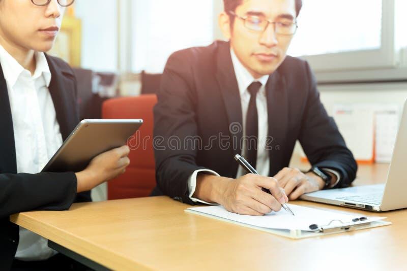 Contratos de firma del ejecutivo de operaciones con la secretaria en el escritorio en oficina fotos de archivo libres de regalías
