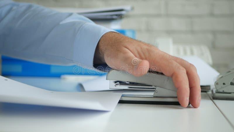 Contratos y documentos del archivo de Job In Office del hombre de negocios usando una grapadora foto de archivo