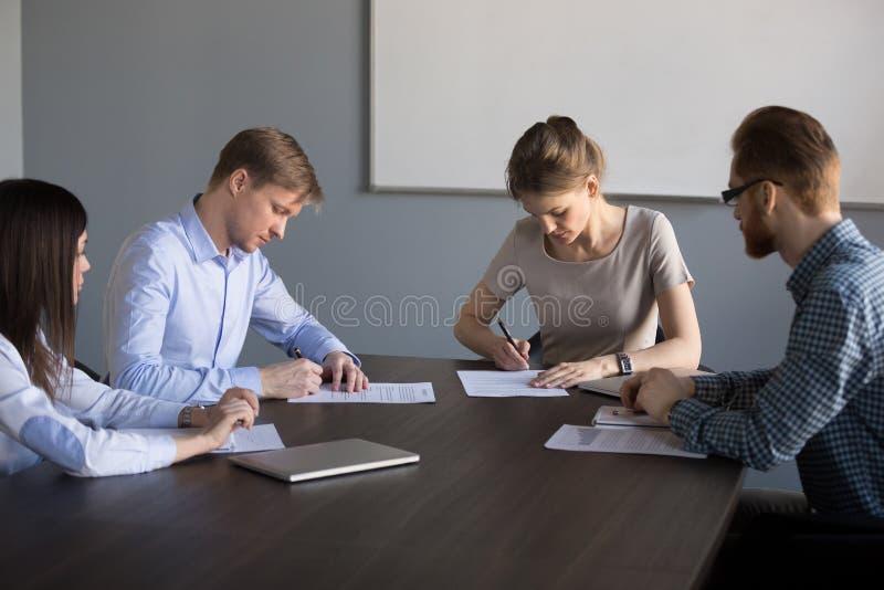 Contrats de signature d'homme d'affaires et de femme d'affaires faisant l'affaire à g photographie stock