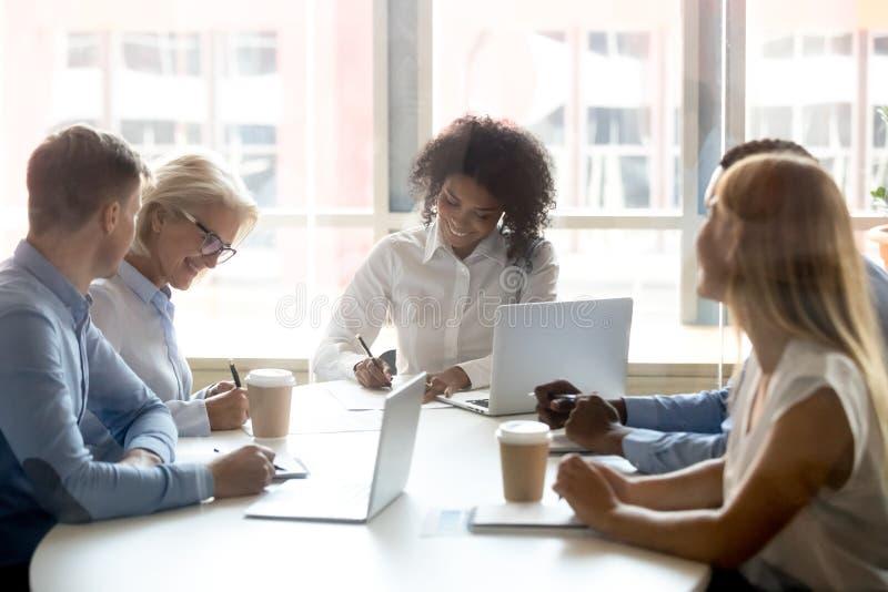 Contratti di firma al concetto di negoziati del gruppo, diverse donne di affari che fanno affare immagini stock
