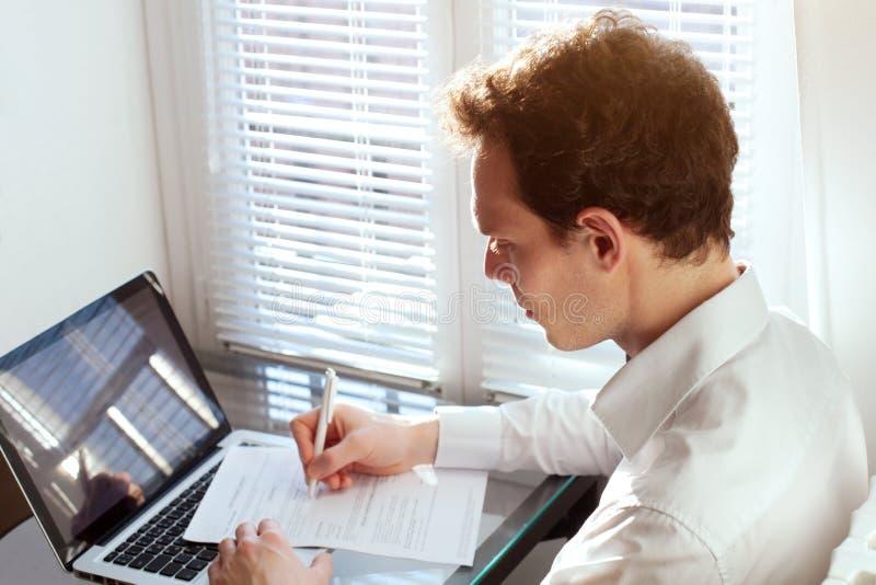 Contratto della lettura dell'uomo d'affari o forma di imposta del materiale da otturazione immagine stock